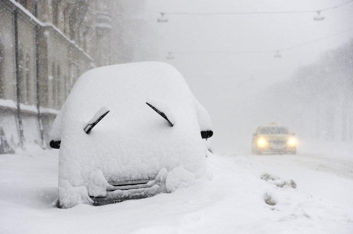Автомобиль под снегом на открытой площадке